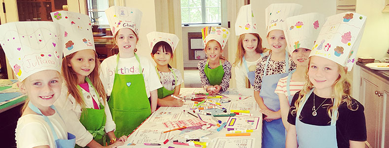 Girls wearing chef hats baking party